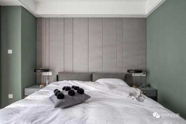 主臥采用人字拼木地板,綠色乳膠漆墻面與拼色窗簾,搭配一盞環形