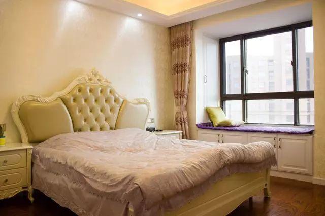 主卧摆了一张欧式大床,房间带有大飘窗,窗户周边是一圈的柜子,不占